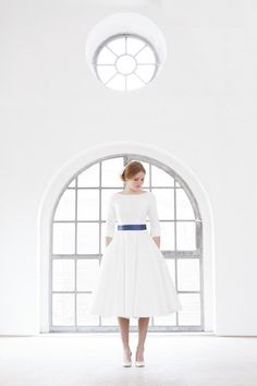 Tea- length wedding gown, bridal dress, with sleeves and cuffs, bateau neckline and low cut back, blue belt and buttons.