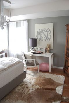 Amazing bedroom with grey walls, West Elm parsons Desk in Glossy White, pink leather Moroccan leather pouf, mercury glass lamp, brown cowhide rug layered over cream flokati rug and Etsy Southern Nest Wooden Monogram. Home Bedroom, Bedroom Decor, Bedrooms, Master Bedroom, Gray Bedroom, Bedroom Office, Bedroom Lamps, Teen Bedroom, Master Bath