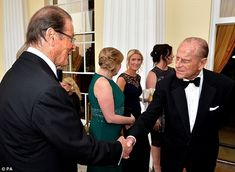 'The name's Philip... Prince Philip': The royal shakes hand with Bond legend Roger Moore