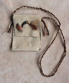 Leather pouch with coyote claw and pheasant feathers by Lupa. At http://thegreenwolf.etsy.com