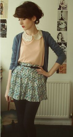 Whimsical peter-pan collared shirt tucked into skirt with thin belt, mismatched cardigan.