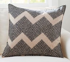"This oversized chevron pattern makes a sophisticated statement in a room. Use it to anchor an arrangement of pillows on a couch or atop a bed. Embellished with fine embroidery, it offers a textural feel and depth.   •24"" square •Made of cotton. •Reverses to solid. •Button closure"