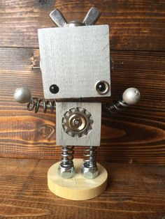 This whimsical little bot was hand-crafted from wood, metal, wire, glass, and found and recycled objects, and is looking for a good home. This