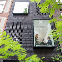 Hidden windows, black brick walls and a large indoor hammock feature in this skinny house that Gwendolyn Huisman and Marijn Boterman designed for themselves.