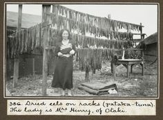 Mrs Henry, of Otaki, with eels drying on racks (pataka-tuna), at Raukawa marae during the opening ceremony of Raukawa meeting house. Photograph taken on 14 March 1936 by George Leslie Adkin.