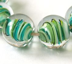 Floating Ribbons Lampwork Tutorial - I think this bead could be made with a clear cylinder base, wrapped with uneven disks in different colours, and then encased in clear to make a round bead - I'll have to experiment.