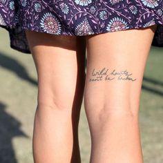 """Pequeño tatuaje en el biceps femoral que dice """"Wild hearts can't be broken"""", frase en inglés que significa """"Los corazones salvajes no se pueden romper""""."""