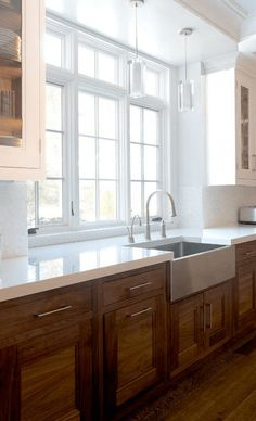 Galley Kitchen Window with white countertops over medium wood cabinets and matching wood floor