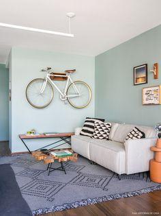 Sala de estar de apto tem parede pintada de verde, sofá bege com almofadas de tricô e bike pendurada na parede.