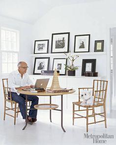 White minimalist kitchen. Love the cabinet/ shelf to prop up framed photos.