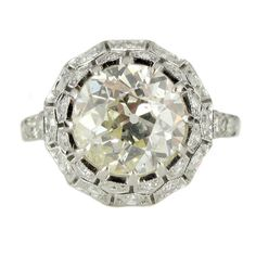 Art Deco 2.65 Carat Diamond Engagement Ring. An exceptional diamond ring from the Art Deco period, circa 1920.   A platinum ring, comprising a large old European cut diamond, weighing approximately 2.65 carats, within a millegrained and pierced dome gallery, decoratively set with small diamonds and chased floral and foliate motif trim.