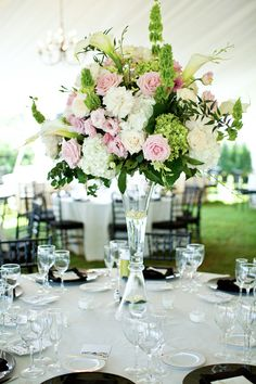 Elegant centerpiece with hydrangeas (white & green), pink & cream roses, pink lisianthus, white callas, green bells of Ireland and some dendrobium stems.