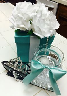 Breakfast at Tiffany's centerpieces on square mirrors for my daughter's birthday party. Paper mache boxes painted with Americana brand paint in Bahama Blue & hot glued satin ribbon. Ribbon tied ivy bowl has acrylic diamonds at the bottom, water & a floating candle. Decorative pearls, glasses & a tiara...