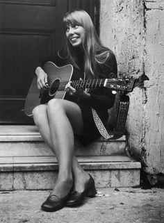 Joni Mitchell plays her guitar outside the Revolution club in London, 1968.