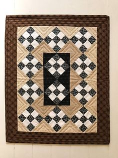Traditional Nine Patch with a twist.  This beautiful quilt has been done in navy, off-white, and beige prints, with a warm brown plaid border. * Quality 100% cotton fabrics, warm-n-natural batting, and soft muslin backing. * Machine pieced and quilted in beige, brown, and black embroidery thread. * Measures 16 1/2 x 20 1/2 long. This quilt art looks great displayed on table or bench, or even as a wall hanging. Classic Nine Patch, whats not to love!  All items are lovingly made in my…