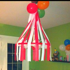 """circus tent"" over the kitchen light fixture. Made from cutting plastic table clothes in strips."