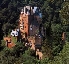 Burg Eltz is a medieval castle nestled in the hills above the Moselle River between Koblenz and Trier, Germany. It is still owned by a branch of the same family that lived there in the 12th century, The castle is surrounded on three sides by the Elzbach River, a tributary on the north side of the Moselle. It is situated on a 70 m rock spur, on an important Roman trade route between rich farmlands and their markets.