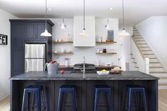 Contemporary cottage kitchen features a white paneled range hood, flanked by stacked floating rustic wood shelves, placed over a stainless steel stove situated next to a wall of navy pantry cabinets enclosing a stainless steel refrigerator.