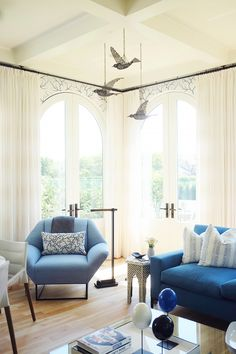 Blue seating area in living space with bird mobile