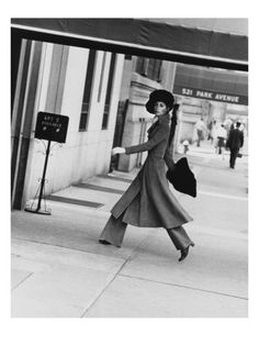 Photographer Jack Robinson captures model Windsor Elliot in midstride as she enters a Park Avenue apartment building in New York. She wears a dove-gray buckskin coat with a high collar and flared hem, wide-leg trousers, and a muskrat muff and matching hat by Harold Rubin. The portrait was published in the August 15, 1968, Vogue.