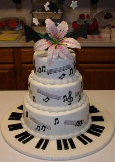 "This buttercream frosted cake is made of 6"", 8"", and 10"" rounds, two per tier. All decorations are made of gumpaste and/or fondant. Topper....Although the Stargazer lily shows up well, the 3 large black music notes do not. You can partially see two of them, one on either side of the lily. There were 75 matching cupcakes to complete this order. All cupcake decorations are made from gumpaste. Cake board is covered in white chocolate fondant and piano keys are white chocolate fondant"