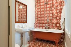 The bedroom opens up into a cheery red tiled en-suite bathroom, featuring a 19th century wooden mirror, Philippe Starck lighting, and a footed bathtub that has been hand-painted red to match the tiles.
