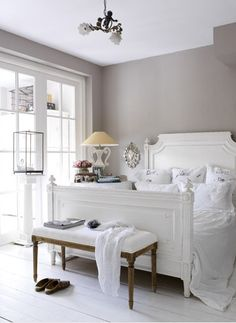 Romantic gray and white bedroom with warm gray walls and white plank floors. Antique chandelier hangs over white bed with wood headboard and footboard covered in soft white bedding. French upholstered bench sits at foot of bed whilst vintage alabaster lamp sits atop skirted bedside table.