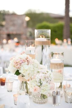 Blush and white hydrangeas with blush peonies and white roses. Floating white tiered glass candles.: