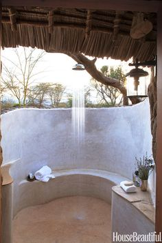 A Kenyan home's thatched roof overhangs the curvaceous, open-air shower by Suzanne Kasler. Click through for more outdoor showers.