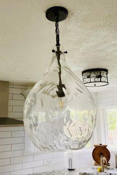 Teardrop Clear Water glass shade 1-light is sure to be a statement maker. Hang a single pendant above the kitchen counter or try a staggered cluster of fixtures above a large dining table. You could flank the sofa or bed with a pair of these glass pendants, letting the shapely form and soft lines set the tone for your farmhouse or coastal-inspired decor. Variations in the texture and size of hand-blown glass reflect distinctive craftsmanship with no two fixtures being exactly the same.