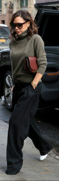 Who made  Victoria Beckham's white shoes, brown sunglasses, green turtleneck sweater, and black pants?
