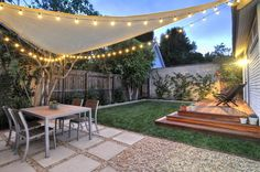 West Hollywood back yard Redwood platform deck, gravel / square paver patio, sail shade, string lights & landscape design.