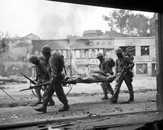 Marines move along a Seoul street with a wounded buddy on a litter Sept. 30, 1950. (AP Photo)