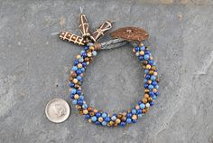 Lapis Lazuli/Picture Jasper/Tiger Eye Kumihimo Artisan Bracelet #bracelet #kumihimo #kumihimobracelet #artisan #artisanbracelet #oneofakind #handmade #handwoven #woven #handknotted #gemstone #natural #naturalgemstones #lapis #lapislazuli #jasper #picturejasper #tigereye #tribal #tribalstyle #boho #bohemian #handcarved #bone #bonebeads #handcarvedbonebeads #coconut #coconutfibrebutton #unique #earthy #lightweight #flexible