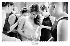 bride being helped getting ready by bridesmaid