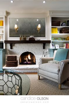 Painted Brick Fireplace •  Cozy Reading Nook with Fireplace • White Painted Fireplace Idea • Recessed Lighting Above Fireplace • Sconces installed in Mirror •  Stained Wood Mantel over White Painted Fireplace • #candiceolson #candiceolsondesign Fireplace Lighting, Fireplace Wall, Fireplace Design, Candice Olsen Design, Candice Olson, White Painted Fireplace, Wood Mantels, Living Room Remodel, Living Rooms
