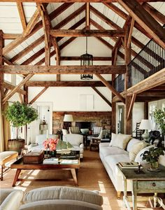 Rustic cabin charm in this expansive living room with exposed wood beams in the vaulted ceiling, shiplap walls and a natural jute rug underneath.