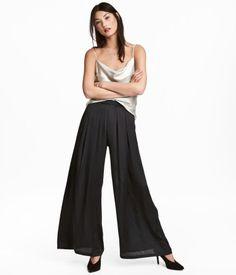 Sort. Vide bukser i let, vævet kvalitet. Bukserne har læg foroven og sidelommer. Skjult lynlås samt hægte og malle i siden. Lange, lige ben.