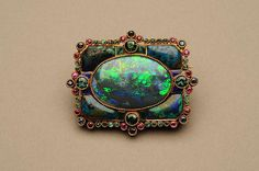 Marie Zimmermann (American, 1879–1972). Brooch, 1920-28.Gold, black opal, shattuckite, green tourmalines, emeralds, sapphires, rubies, and enamel. The Metropolitan Museum of Art, New York. Gift of Jacqueline Loewe Fowler, 2011 (2011.10.2). #opal #jewelry