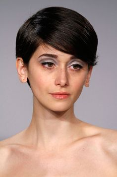 Pale silver blue eyes and pale pink lips with short dark hair. Simple but elegant.