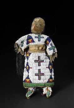 """Sioux beaded doll. Clothed in an ornate fully-beaded bodice and dress bottom, decorated in conjoined diamonds, tipi motifs and crosses, her head with remains of pigment, edge-beaded, and with a horsehair coiffure, a porcelain doll arm seen below one of the fringed sleeves, wearing a printed cloth petticoat and beaded moccasins and leggings.  height 12in;  """"The attention to detail in every step of the creative process during its construction not only reflects a talented an..."""