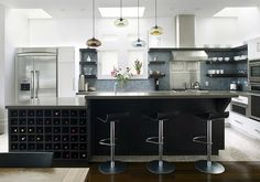 Modern contemporary kitchen design with ebony kitchen cabinets, black kitchen island, marble counter tops, frosted glass backsplash, vintage architect's stool and exposed brick wall. Kitchen Island Lighting Modern, Kitchen Island With Seating, Kitchen Pendant Lighting, Kitchen Pendants, Pendant Lights, Kitchen Modern, Kitchen Islands, Glass Kitchen, Glass Pendants