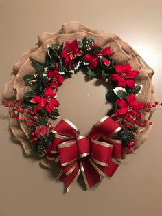 This beautiful burlap wreath is made with holly and poinsettia garland, holly berries, Christmas picks and a big gold and burgundy bow. The approximate diameter is 24.