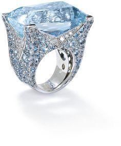 An aquamarine and diamond ring, by Vita. The rectangular-shaped aquamarine, estimated to weigh approximately 59 carats, to a pavé-set aquamarine bezel and similarly set diamond chevron gallery