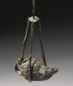A roman bronze lamp in the form of the head of a sleeping African boy, three bronze suspension chains, the filling hole held in the mouth of the boy (1st-2nd AD)  Sotheby's