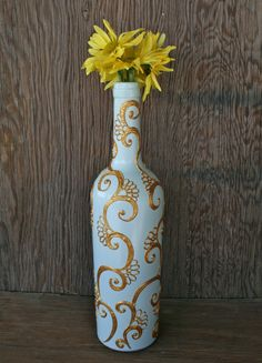 Hand Painted Wine bottle Vase, Up Cycled, Light Blue with Gold filigree, Dramatic Henna style design. $25.00, via Etsy.