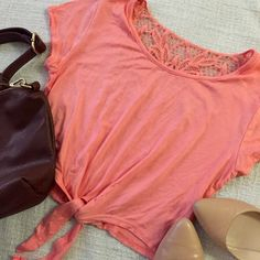 """coral crop tie shirt Coral cropped tie shirt with lace back. Never worn before, but has so many possibilities! 95% Rayon, 5% Rayon. Vey soft! No trades.  Measurements:   Length 16.5"""" Shoulder to shoulder 14"""" Armpit to armpit 16.5"""" E {hanger} M Tops Crop Tops"""