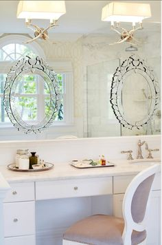 Bathroom Ideas. A custom white and light gray linen chair was used here along with venetian mirrors which were glued over a larger mirror to provide a continuity of reflective effect. The sconces come from Circa Lighting. Wallpaper is from Romo. #Bathroom #BathroomDesign #BathroomDecor