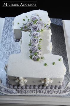 "First Communion #82Religious This cake is shaped like the number ""one'"" to rrepresent someone's First Holy Communion. A beautiful bed of roses in the shape of a cross are also added on top. Glitter was sprinkled all over the cake to give it a special glow."