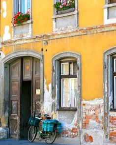 Sopron Hungary Photography Print - Yellow Artwork - Windows and Bicycles in Sopron. Rustic european decor for your home. Photography print featuring yellow walls, an open door, windows and a bicycle. This photograph from Hungary captures the old city of Sopron. Available in a variety of standard sizes and finishes. Sold unframed and does not include mat.
